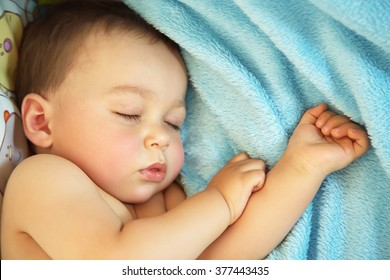 sleeping baby. little boy lying in a crib on a blue blanket