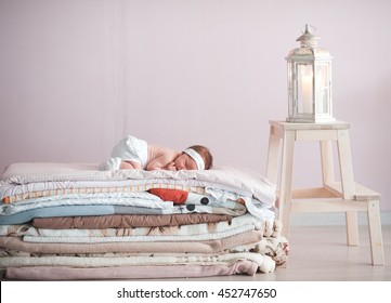 Sleeping baby lying on stack of blankets in room. Childhood