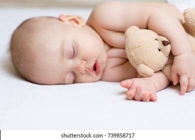 Sleeping baby newborn in bed, holding a teddy bear.