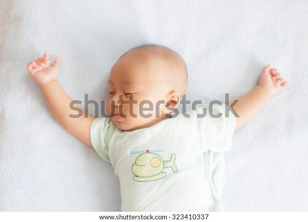 Bebé dormido en la espalda sobre una cama blanca