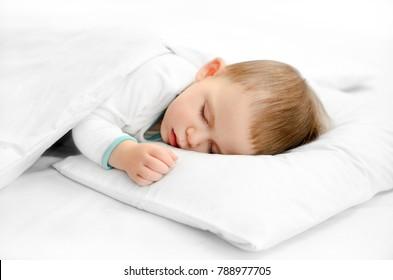 Sleeping baby on white background. Toddler boy in pijama sleeps on white pillow