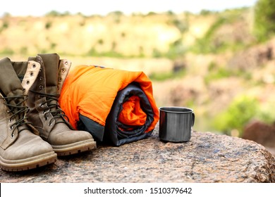 Sleeping bag, cup and boots outdoors on sunny day