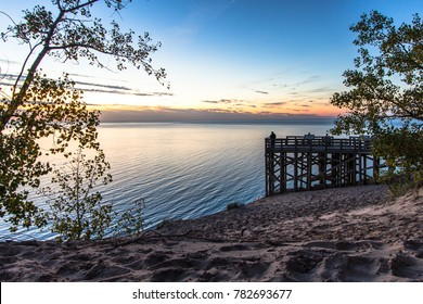 Sleeping Bear Dunes National Lakeshore, Large wooden overlook at sunset with silhouette of tourist admiring the sunset at the famous Sleeping Bear Dunes National Park in Michigan.