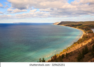 Sleeping Bear Dunes and South Manitou Island. Seen from Empire Bluff Trail in northern Michigan. Autumn colors dot the landscape and puffy clouds float in the blue sky.
