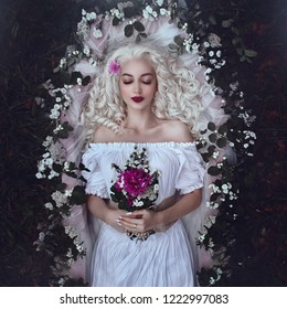 Sleeping beauty. Enchanted Princess lies in a coffin in flowers with a bouquet. Sleeping in the dark woods. Fabulous beautiful white Queen.