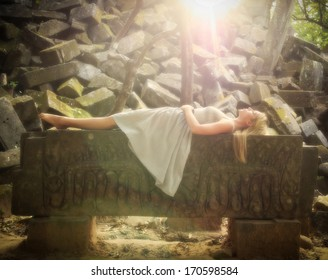 Sleeping Beauty fairytale princess lying down on a stone altar in the forest.