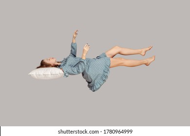 Sleeping beauty floating in air. Relaxed girl in vintage ruffle dress keeping eye closed, lying on pillow levitating, flying in dream with hands up to catch. studio shot isolated on gray background