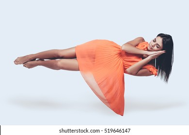 Sleeping beauty. Full length studio shot of attractive young woman in orange dress hovering in air and keeping eyes closed