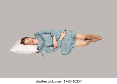 Sleeping beauty hovering in air. Relaxed girl in vintage ruffle dress lying comfortably on pillow levitating, keeping eyes closed, watching dreams. full length studio shot isolated on gray, indoor - Shutterstock ID 1765410257