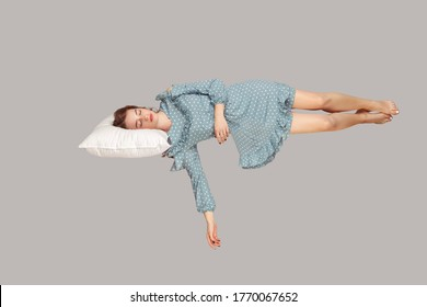 Sleeping beauty hovering in air. Relaxed girl in vintage ruffle dress lying comfortably on pillow levitating, keeping eyes closed, watching dreams. full length studio shot isolated on gray, indoor