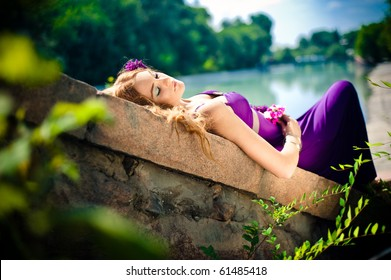 The sleeping beauty lays on stones near to the river