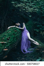 Sleeping Beauty lies on a log. Background fairy forest. Sad Princess, crying. Luxury purple dress. Fashionable toning