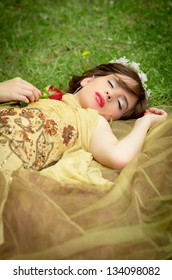 SLEEPING BEAUTY lying on the grass in the forrest with a rose