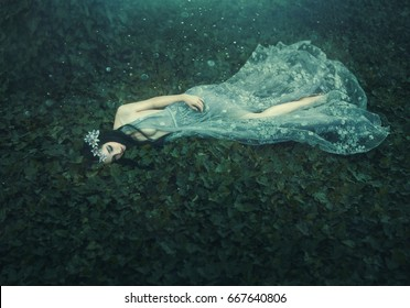 Sleeping Beauty. Woman lies on green grass ivy in dark, dense forest. unusual transparent grey dress. Artistic processing photography. Vintage design. Dreaming nymph greek nature mysterious goddess