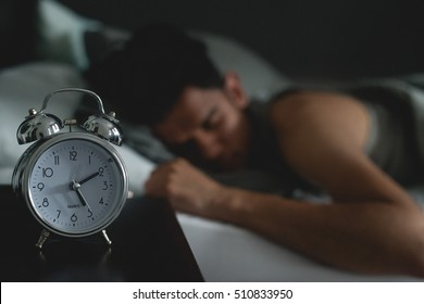 Sleeping in bed with alarm clock