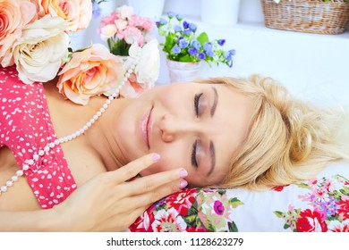 Sleeping blond woman lying on pillow among flowers