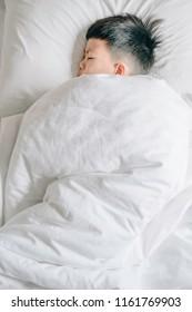 Sleeping boy, cute Asian boy sleeping on white pillow at home