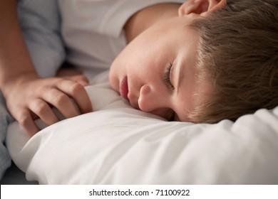 Sleeping boy on the white pillow