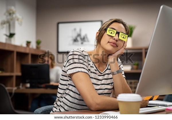 Femme d'affaires endormie qui se couvre les yeux avec des notes collantes sur les lunettes. Jeune femme se repose les yeux sur des notes adhésives. Fille penchée à la main, couvrant les spécifications avec des notes collantes à l'oeil ouvert.
