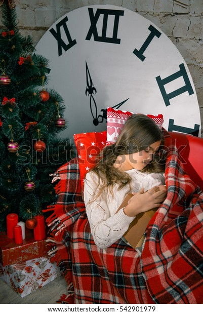 Sleeping child in bedroom. Kid at home. Christmas Xmas New Year winter holiday concept. Dream New Year's Eve, New Year's Eve Dream,  Girl read the book and fell asleep on the couch, covered  blanket