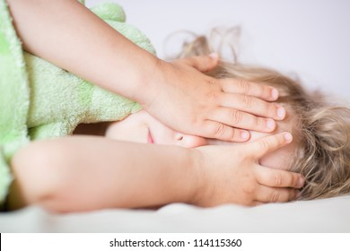 Sleeping child cover face with hands and doesn't want to wake up