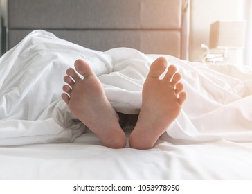 Sleeping comfort relaxation, world sleep day and bedtime insomnia concept with young girl's bare foot laying lazy on bed resting in comfy hotel bedroom on white bed sheet