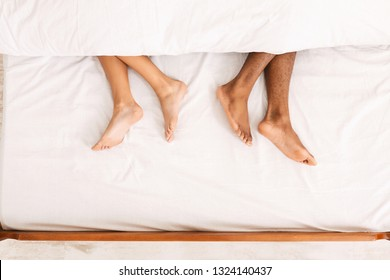 Sleeping couple. Male and female bare feet under duvet lying on bed separately, top view