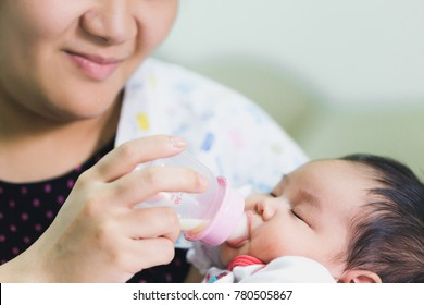 Sleeping of Cute baby with a milk bottle,Baby Feeding. Happy Asian woman or Mother feeds the baby bottle. close up newborn being drinking milk from a bottle her mother. drink and healthcare concept