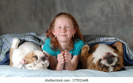 sleeping with the dogs - child with two bulldog in bed