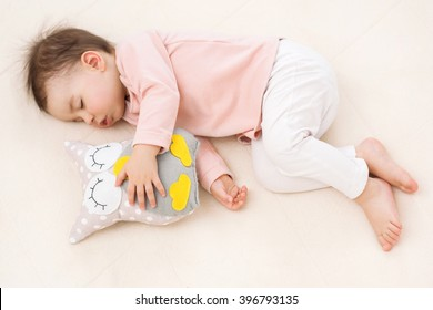 Sleeping and dreaming beautiful baby girl toddler with an owl toy on the bed