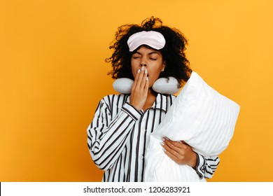 Sleeping. Dreams. Woman portrait. Afro American girl in pajama and sleep mask is holding a pillow and yawning, on a yellow background