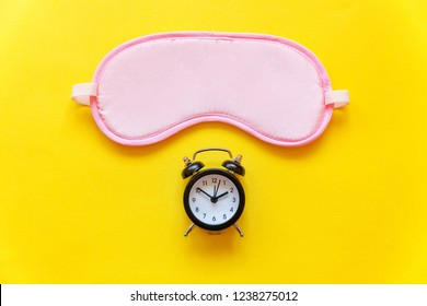Sleeping eye mask, alarm clock isolated on yellow colourful trendy background. Do not disturb me, let me sleep. Rest, good night, siesta, insomnia, relaxation, tired, travel concept