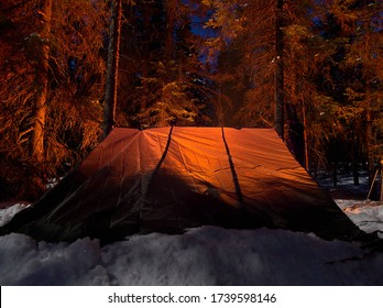 Sleeping in Finnish lean-to shelter Laavu in winter taiga forest.