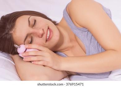 Sleeping girl , asleep with alarm clock in the bed.