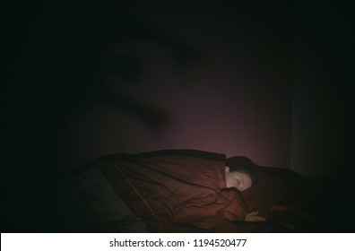 Sleeping girl in the bed and shadow of monster on the wall behind. Nightmare concept.