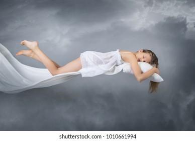 Sleeping girl. Flying in a dream. Clouds on grey background. Sleep