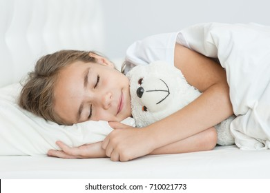 Sleeping girl hugging a toy bear