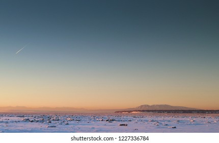 Sleeping Lady MT Susitna, Cook Inlet Alaska at dusk in winter with ice and snow as seen from Anchorage