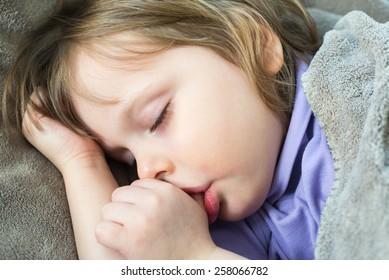 Sleeping little cute baby sucking thumb