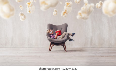 Sleeping little spectator with popcorn in the cinema