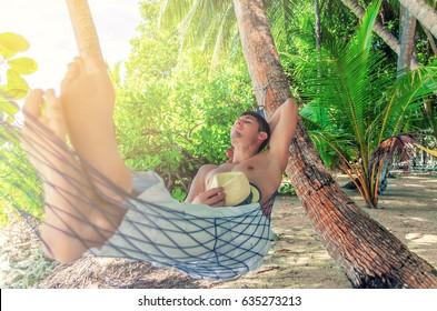 Sleeping man in a hammock under a palm tree