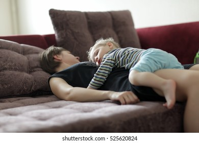 Sleeping mother and boy on a sofa at home