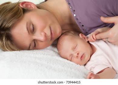 Sleeping mother with her sleeping 18 days old baby