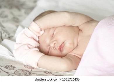 sleeping naked newborn baby girl on a blanket