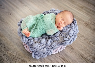 Sleeping newborn baby in a basket. Infant lovely wrapped. Top view.