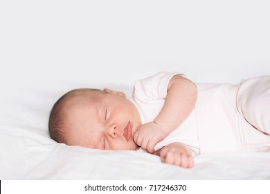 Sleeping newborn baby in a bodysuit on white blanket background. Beautiful portrait of little child girl 14 days, two week old.