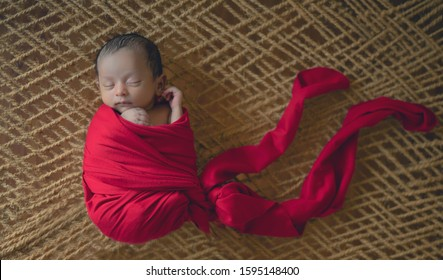 sleeping newborn baby boy wrapped in red cloth, 1 month old baby lying on latticework