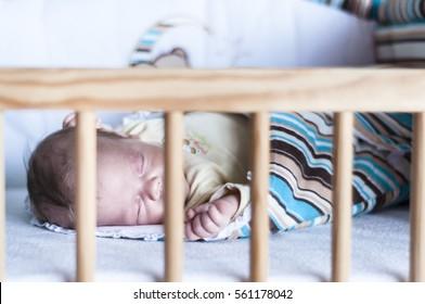 The sleeping newborn baby in the crib