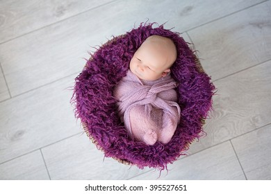 sleeping newborn baby girl on purple fur in a basket