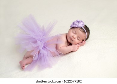 Sleeping, newborn baby girl wearing a lavender colored, crocheted, flower headband and light purple, tulle tutu.